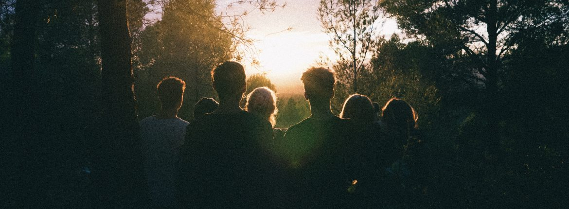 Silhouette of a group of people standing in a forest looking towards a sunset